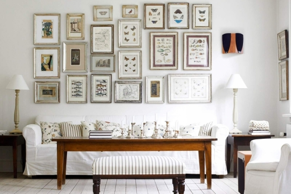 многочисленные картины на стене над диваном